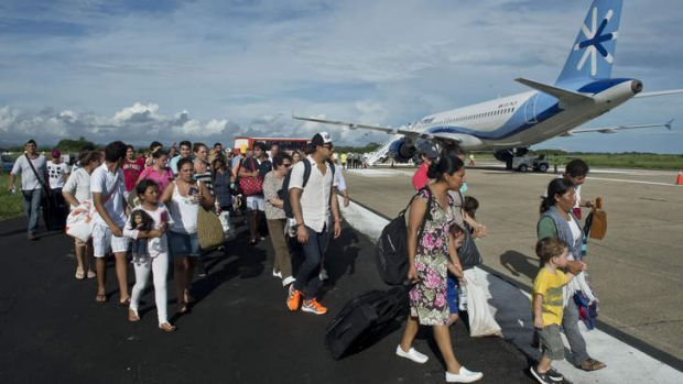Tourists wait for their flight at the airport of Acapulco. Mexican authorities scrambled to airlift tens of thousands of ...