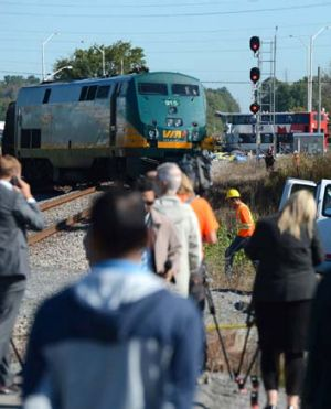 Crash site: A city bus is severely damaged after colliding with a Via Rail passenger train at a crossing.