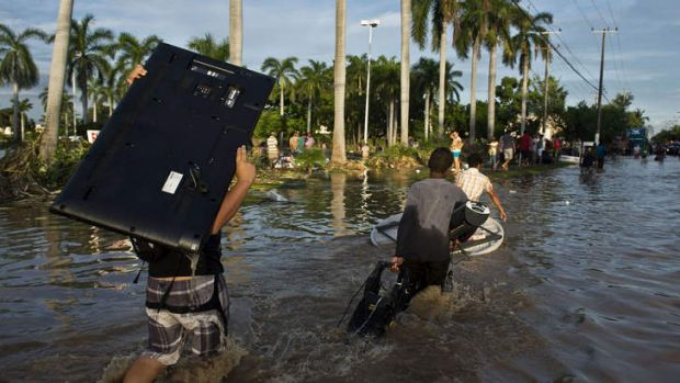 Looters carry goods from a supermarket in Acapulco, Mexico as heavy rains hit the country.