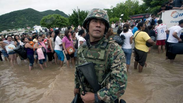 A Mexican Navy member stands guard in a flooded area of Acapulco, Mexico. The official death toll rose to 47 after the ...