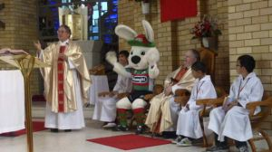Glory be: Father Jersey and Charlie the Rabbit lead the congregation in a rendition of the South Sydney victory song at ...