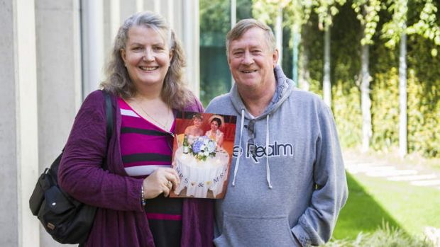 Julia and Barry Rollings at the Legislative Assembly on Thursday with a photo of their daughter's wedding in the US.
