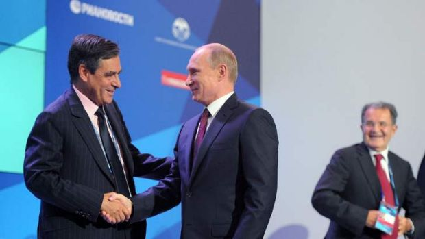 Russian President Vladimir Putin, centre,  shakes hands with former French Prime Minister Francois Fillon. Mr Putin was ...