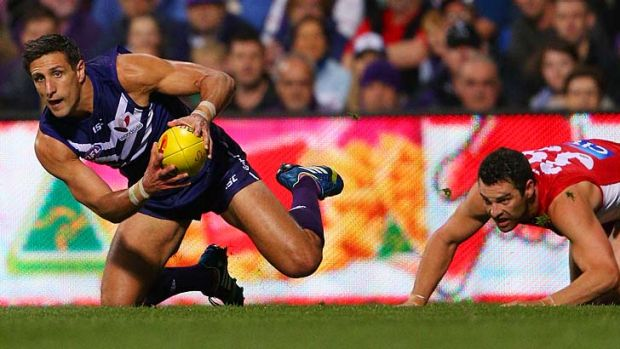 Fremantle captain Matthew Pavlich grabs a mark ahead of Heath Grundy of the Swans.