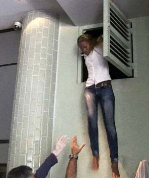 A woman escapes via an air vent where she was hiding during an attack by masked gunmen at a shopping mall in Nairobi.