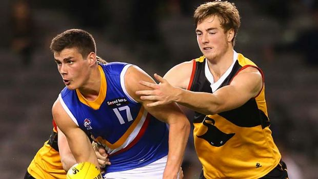 Likely top draft pick Thomas Boyd gets a handball away under pressure.
