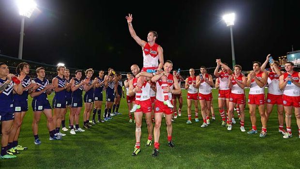 Jude Bolton gets carried off by Jarrad Mcveigh and Ryan O'Keefe during the AFL Second Preliminary Final match between ...