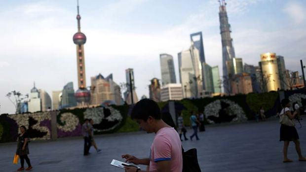 A man checks his iPad in front of the financial district in Shanghai, China.