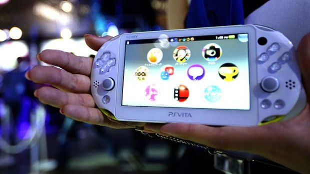 A model holds a Sony Computer Entertainment Inc. PlayStation Vita (PS Vita) portable video game player at the Tokyo Game ...