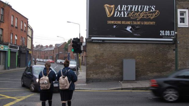 Morning commuters pass a billboard advertising Arthur's Day in Dublin, Ireland.