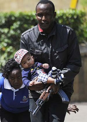 Rescued: A policeman carries a baby to safety after the attack on the Westgate mall.