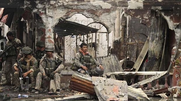 Victory: Troops rest amidst the ruins in Zamboanga.