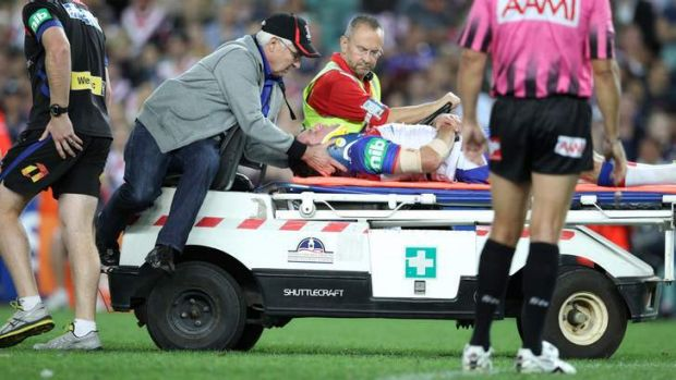 Down and out: Retiring Knights star Danny Buderus is taken from the field after colliding with Jared Waerea-Hargreaves.
