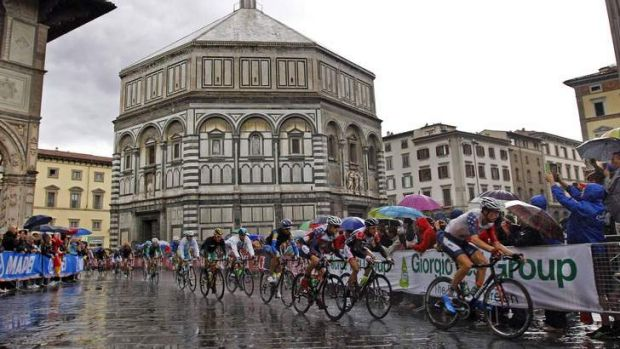Riders cycle under heavy rain next to the San Giovanni Baptistery during the men's elite road race in Florence, Italy.