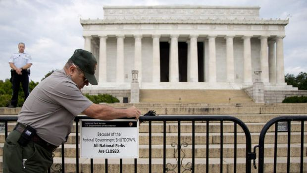 A US Park Police officer watches at left as a National Park Service employee posts a sign on a barricade closing access ...