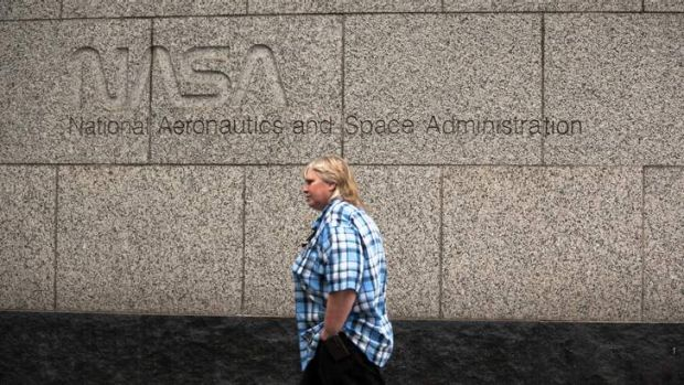 A woman walks past the NASA headquarters on Tuesday morning after the federal government shutdown. NASA turns 55 today, ...