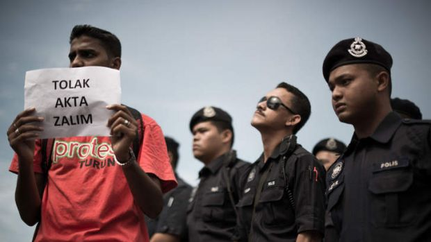 """A protester holds a sign reading """"no to cruelty act""""  outside Parliament in Kuala Lumpur."""