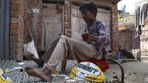 A 13-year-old boy stitches Summit rugby league balls outside his home in northern India.
