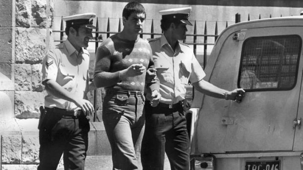 Back in the day: Mark 'Chopper' Read is escorted to a police divvy van.