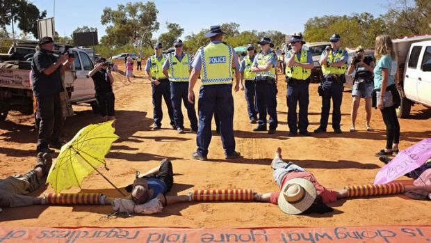 Protestors locked together block the road to Woodside's proposed gas factory at James Price Point on Western Australia's ...
