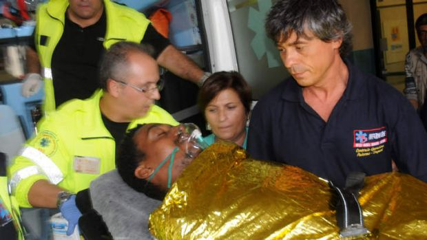 A man is carried off an ambulance at the Palermo Civico hospital, Italy, after being rescued off the Italian island of ...