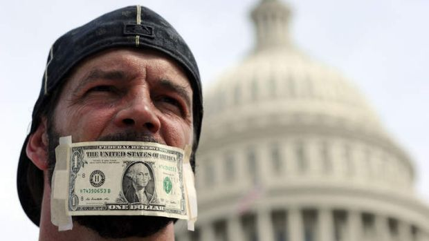 A protester has his mouth covered with a dollar bill during a demonstration in Washington DC, urging congress to end the ...