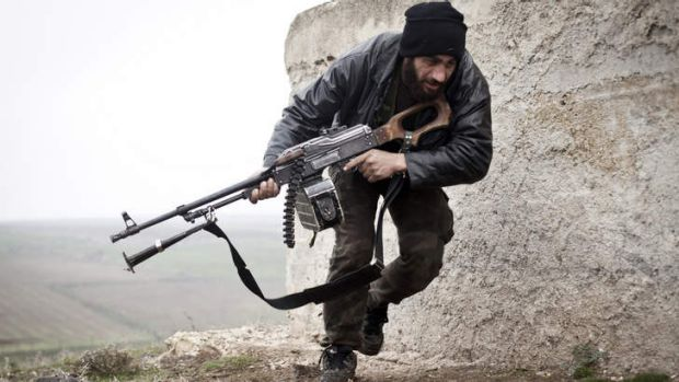 Bitter standoff: A Free Syrian Army fighter takes cover during fighting with the Syrian Army in Azaz last year.