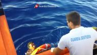 A still image taken from video released by the Italian Coast Guard shows migrants being rescued from the water off the ...