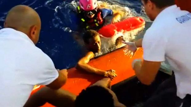 This scene from a video shows rescuers helping a survivor of the capsized immigrant boat to safety off the Italian ...