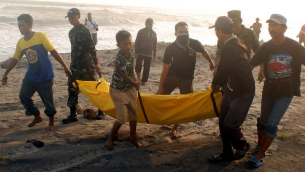 Rescuers with a victim of the boat sinking off Java.