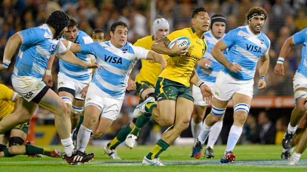 Way through: Australia's Israel Folau breaks the Pumas line to score one of his three tries for the Wallabies in Rosario ...