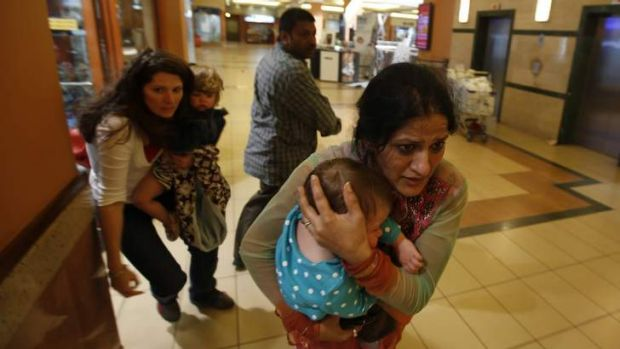Women carrying children run for safety as armed police hunt gunmen who went on a shooting spree in Westgate shopping ...