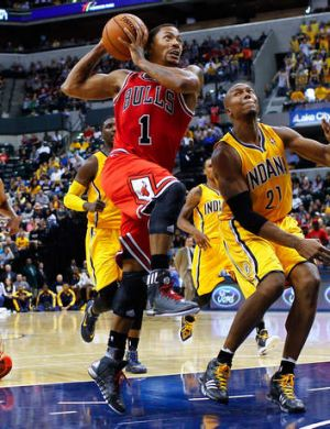 Back in action: Chicago Bulls star Derrick Rose takes the ball to the hoop against David West of the Indiana Pacers at ...