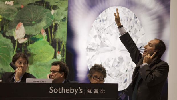 A Sotheby's phone auctioneer gestures during an auction that saw a 118.28-carat white diamond break a world record.
