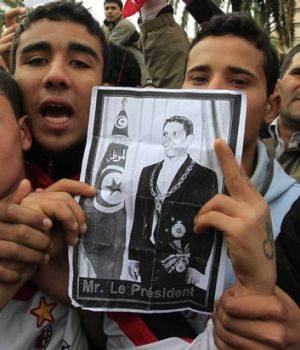 Tunisian protesters chant as they hold a photograph of Mohammed Bouazizi in January 2011.