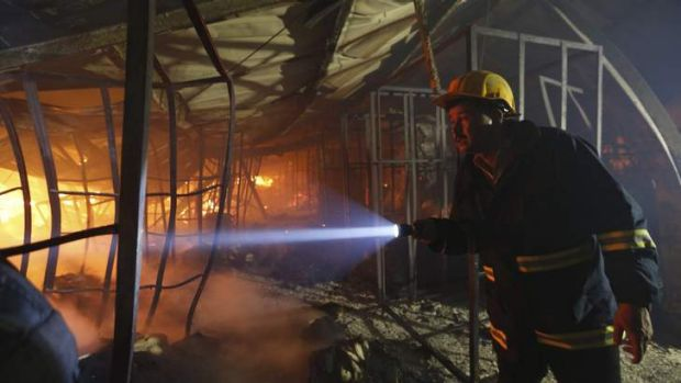 A firefighter inspects a fire inside a garment factory in the Bangladeshi town of Gazipur. Nine employees died in the blaze.