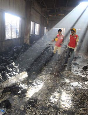 Ruins: Bangladeshi rescue workers examine what remains of the factory.