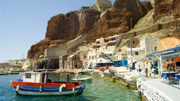Boats tied along the shore and dockside restaurants, Oia, Santorini.