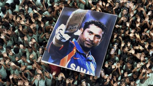 Indian students hold a poster of Indian cricketer Sachin Tendulkar after he batted for his landmark 100th century ...