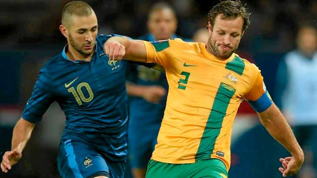Struggling: Lucas Neill tangles with Karim Benzema of France.