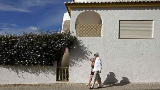 Crime scene: Tourists walk under the windows of the  apartment where Madeleine McCann disappeared.
