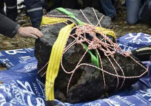 A meteorite that exploded over Russia in February is displayed on the bank of the Chebarkul Lake.