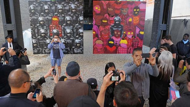 A crowd gathers to view Banksy's latest work in the Chelsea neighborhood of New York City.