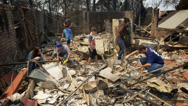 Aftermath of the Winmalee bushfire on Emma Pde. The Kozumplik family sifts through the rubble of what used to be their ...
