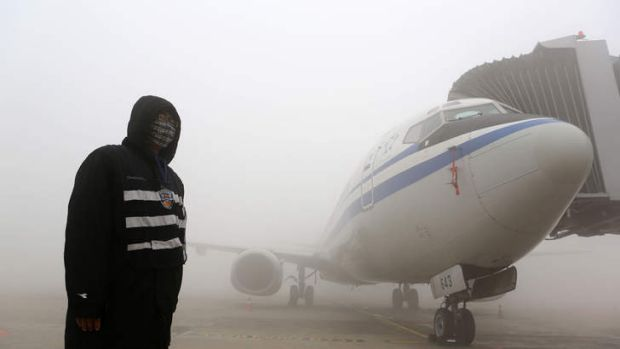 A man stands next to an aeroplane under heavy smog in Harbin.