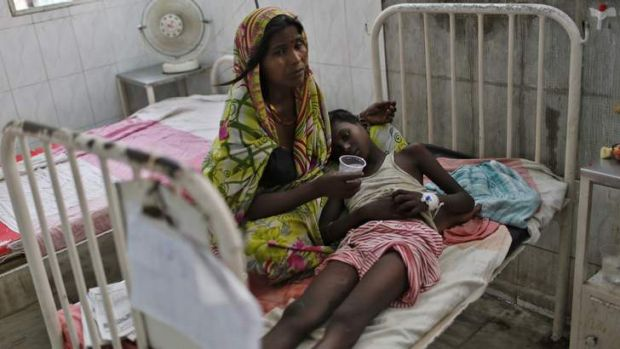 A sick boy lies on his mother's lap inside a hospital after he consumed one of the contaminated meals.