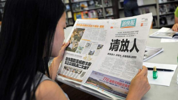 """A woman reads the New Express newspaper that carried a full-page editorial with headline """"Please release our man"""", in a ..."""