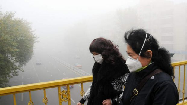 Pedestrians wearing masks walk along a road as heavy smog engulfs the city in Harbin, China. China is attempting to cut ...