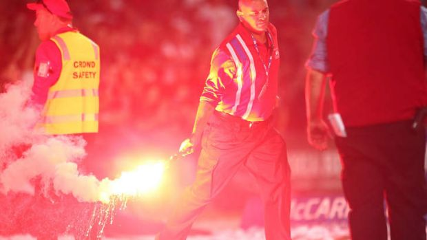 A security guard handles a flare during the round three A-League match between Sydney FC and the Western Sydney ...