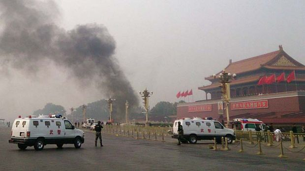 Crash: Police cars block off the roads leading into Tiananmen Square as smoke rises into the air after a ...
